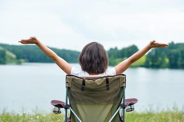 Młodej kobiety freelancer siedzi na krześle i relaksuje w naturze blisko jeziora. aktywność na świeżym powietrzu w lecie.