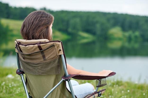 Młodej kobiety freelancer siedzi na krześle i relaksuje w naturze blisko jeziora