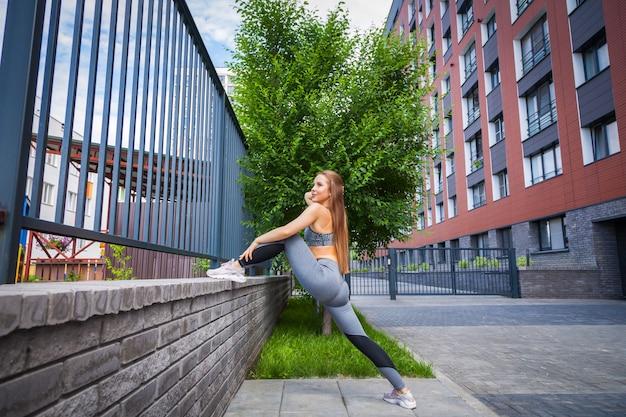 Młodej kobiety gimnastyczka z szczupłą sylwetką w sportswear robi rozciąganiu na miasto ulicie w ciepły letni dzień. rozciąganie na świeżym powietrzu