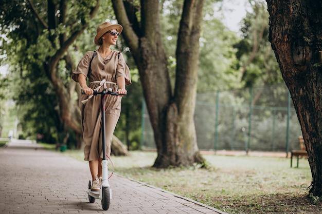 Młodej kobiety jeździecka hulajnoga w parku