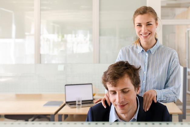 Młodej kobiety kładzenia ręki na mężczyzna ramionach w biurze