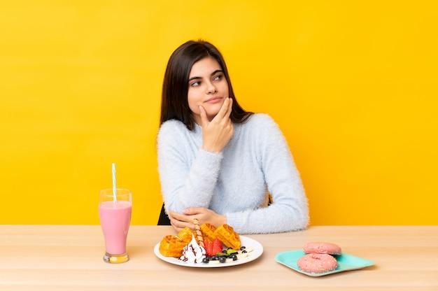Młodej kobiety łasowania gofry i milkshake w stole nad kolor żółty ścianą myśleć pomysł