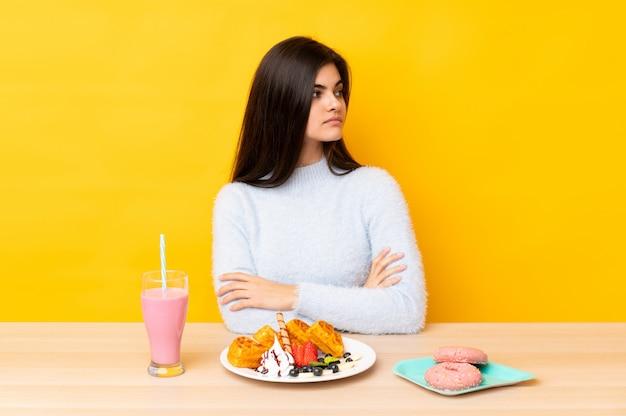 Młodej kobiety łasowania gofry i milkshake w stole nad kolor żółty ścianą patrzeje stronę