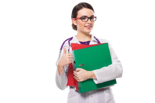 Młodej kobiety lekarka z stetoskopu mienia segregatorami w jej rękach z kciukiem up w bielu mundurze na bielu