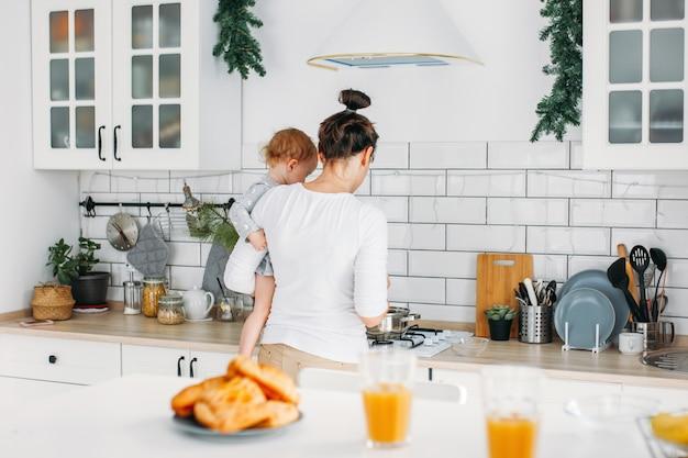 Młodej kobiety mama z dziewczynką na rękach gotuje śniadanie na jaskrawej kuchni w domu