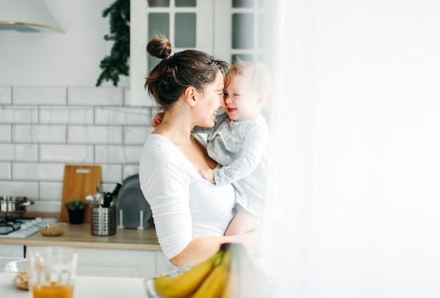 Młodej kobiety mama z dziewczynką na rękach ma zabawę i kulinarnego śniadanie na jaskrawej kuchni w domu