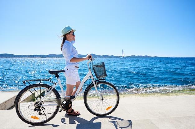 Młodej kobiety miasta jeździecki rowerowy pobliski morze