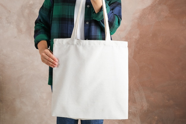 Młodej kobiety mienia dużego ciężaru torba przeciw brown tłu