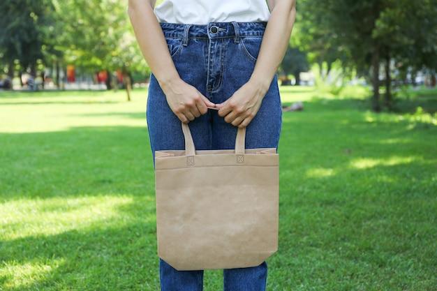 Młodej kobiety mienia dużego ciężaru torba przeciw greenery tłu