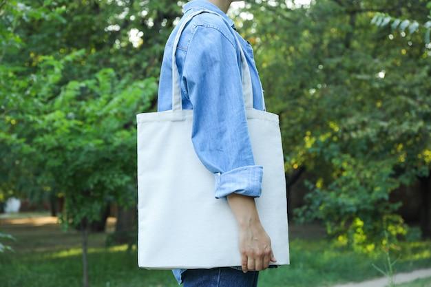 Młodej kobiety mienia dużego ciężaru torba przeciw zieleni