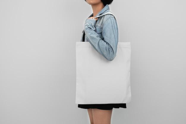 Młodej kobiety mienia eco bawełniana torba odizolowywa na bielu