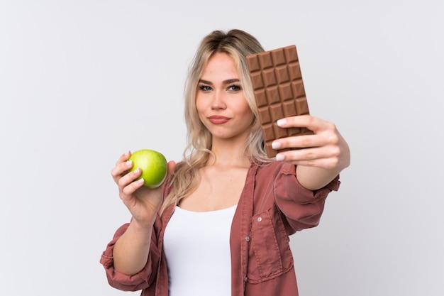 Młodej kobiety mienia jabłko czekolada nad odosobnionym tłem