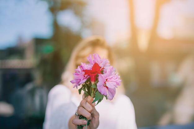 Młodej kobiety mienia kwiatu bukiet przed jej twarzą przeciw zamazanemu tłu