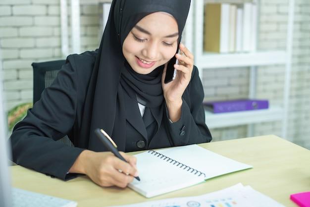 Młodej kobiety muzułmańska praca w biurze używać telefon