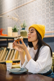 Młodej kobiety oblizania wargi i mienia deserowa pobliska filiżanka przy stołem