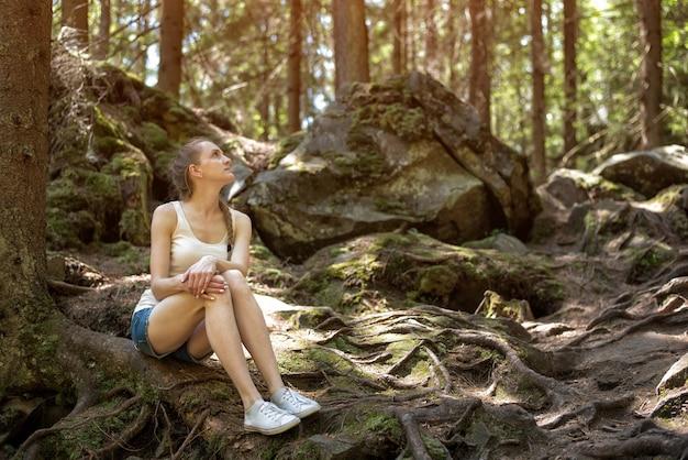 Młodej kobiety obsiadanie na korzeniach drzewa w dzikim lesie. bajkowy las i nowoczesna śnieżna biel.