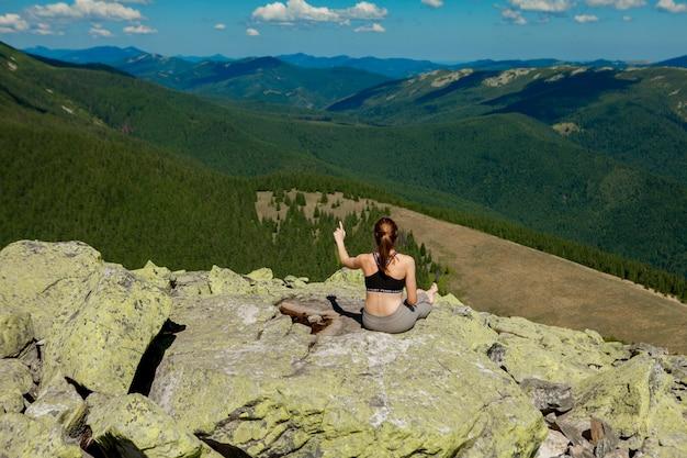 Młodej kobiety obsiadanie na skale i patrzeć horyzont.