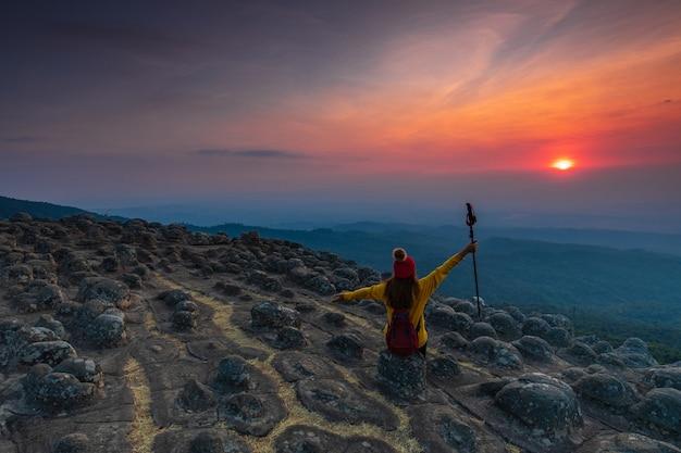 Młodej kobiety obsiadanie na skale w górach