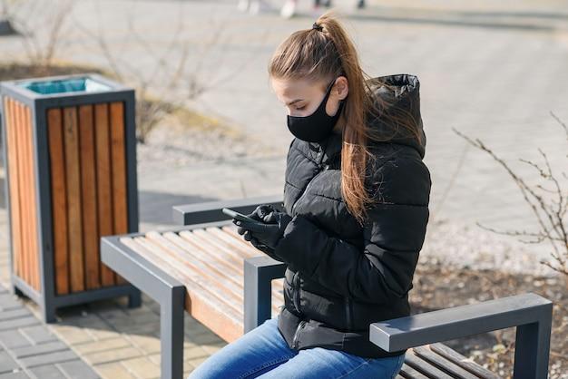Młodej kobiety obsiadanie na ulicznej ławce z medyczną maską i czerni ubraniami