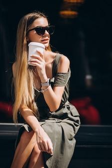 Młodej kobiety obsiadanie na zewnątrz kawiarni pije kawę