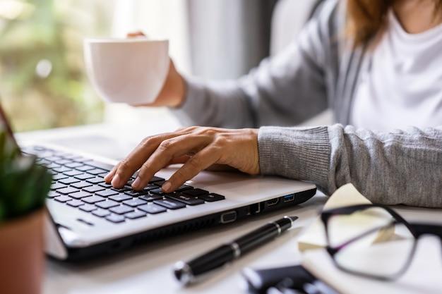 Młodej kobiety obsiadanie przy żywym pokojem i działanie na laptopie i smartphone w domu