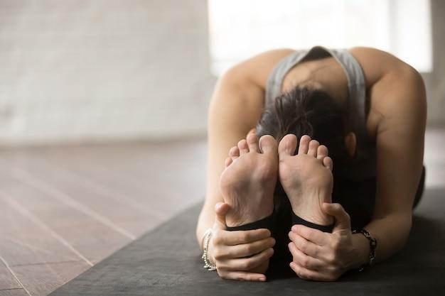 Młodej kobiety obsiadanie w paschimottanasana ćwiczeniu, pracowniana podłoga