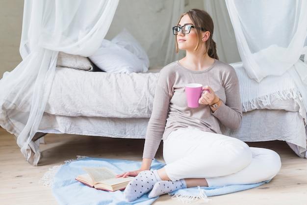 Młodej kobiety obsiadanie w sypialni trzyma filiżankę kawy z książką