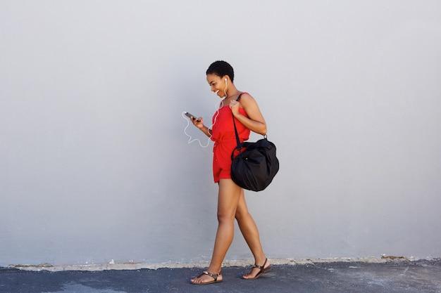 Młodej kobiety odprowadzenie i słuchanie msuic na telefonie komórkowym