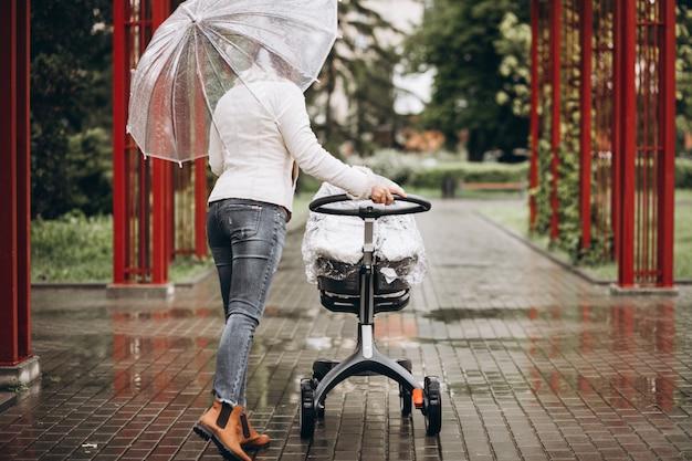 Młodej kobiety odprowadzenie z wózkiem pod parasolem przy słabą pogodą
