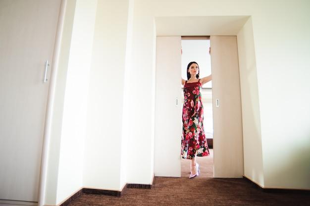 Młodej kobiety otwarcia drzwi przy nowożytnym pokojem hotelowym.