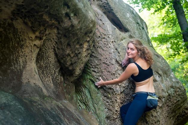 Młodej kobiety pięcie na wielkich głazach plenerowych