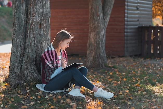 Młodej kobiety pozycja blisko drzewnego dalekiego strzału