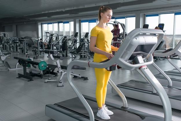 Młodej kobiety pozycja na karuzeli przed bieganiem w gym