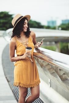Młodej kobiety pozycja na miastowym moscie z wynos kawą i używać smartphone