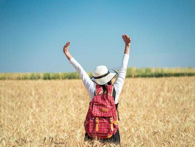 Młodej kobiety pozycja na złotym pszenicznym polu