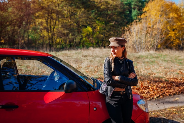 Młodej kobiety pozycja samochodem na jesieni drodze. kierowca zatrzymał auto w lesie, aby cieszyć się jesiennym krajobrazem