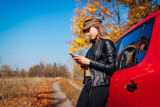 Młodej kobiety pozycja samochodem używać smartphone na jesieni drodze. sterownik zatrzymał auto, aby złapać lepszy sygnał