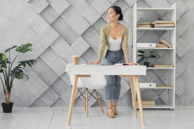 Młodej kobiety pozycja w jej biurowym długim strzale