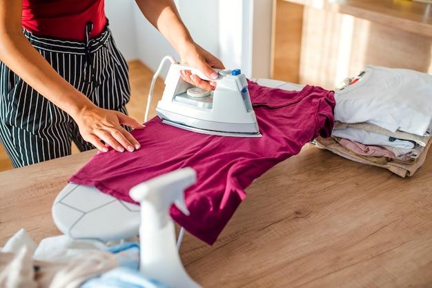 Młodej kobiety prasowania odziewa na prasowanie desce