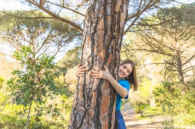Młodej kobiety przytulenia drzewo w lesie