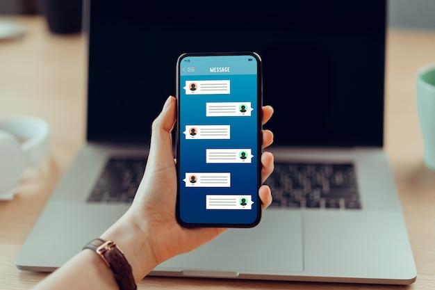 Młodej kobiety ręka trzyma smartphone i pokazuje powiadomienie wiadomości czatu nowego ekranu. koncepcja sieci społecznościowej.