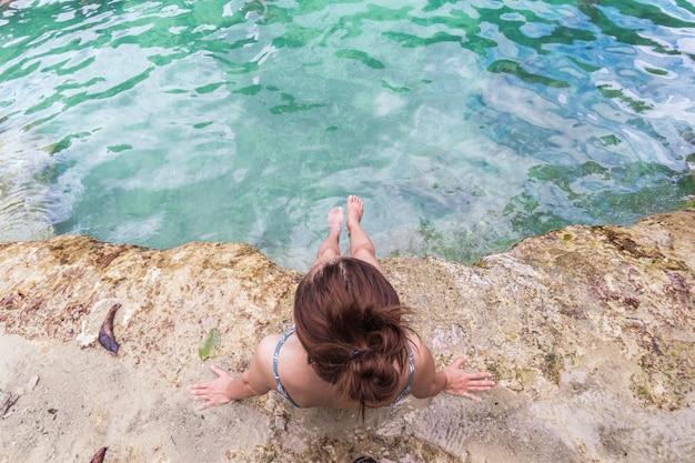Młodej kobiety turystyczny obsiadanie i relaksować przy szmaragdowym basenem w krabi, tajlandia