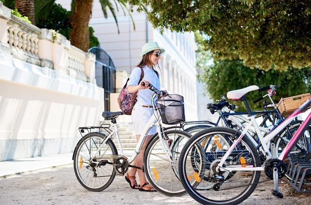 Młodej kobiety turystyczny rowerzysta z miasto bicyklem w miasteczku blisko morza