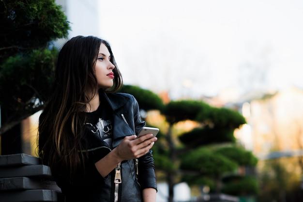 Młodej kobiety writing wiadomość na telefonie komórkowym w ulicznej kawiarni. patrząc w dół