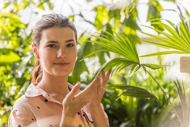 Młodej kobiety wzruszająca roślina w zielonym domu