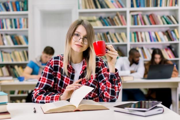 Młodej ładnej blond kobiety czytelnicza książka i pić kawa przy stołem w nowożytnej szkoły wyższa bibliotece