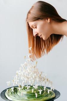 Młodej niezwykłej dziewczyny kreatywnie konceptualny portret. ładna kobieta w białej sukni w stylu greckim pachnące oryginalną kompozycję bukiet kwiatów wiosna kryty. miękkość, łatwość, delikatność. szczęście, radość życia