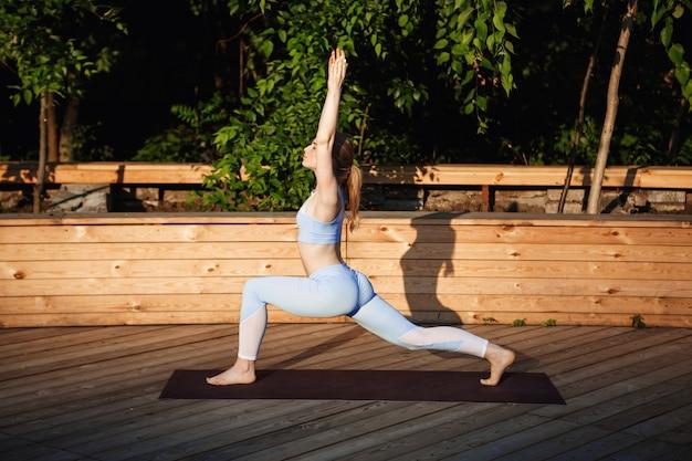 Młodej pięknej blondynki dziewczyny ćwiczy joga outside przy wschodem słońca.