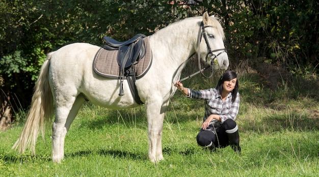 Młodej pięknej brunetki kobiety jeździecki koń