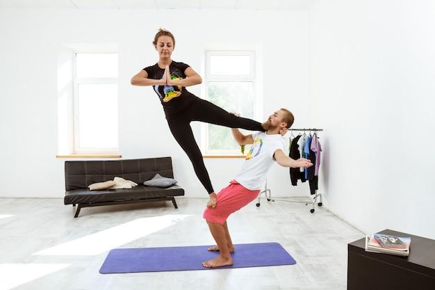 Młodej pięknej sportive pary ćwiczy joga asany w domu.